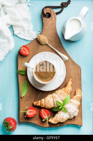 Le petit-déjeuner ou un dessert. Des croissants frais avec des fraises, une tasse de café et de lait en bouteille Banque D'Images