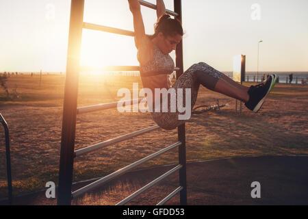 Coup franc de forme et en santé woman hanging soulève la jambe sur la station de remise en forme en plein air au Banque D'Images