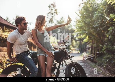 Photo de couple sur selfies moto. Young man and woman taking self portrait alors que sur moto sur route du village. Banque D'Images