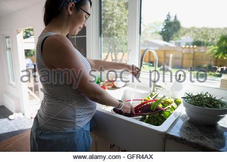 Femme enceinte laver les légumes à l'évier de cuisine Banque D'Images