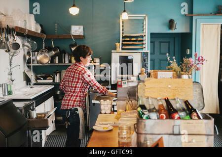 Une femme travaillant derrière le comptoir dans un café Banque D'Images