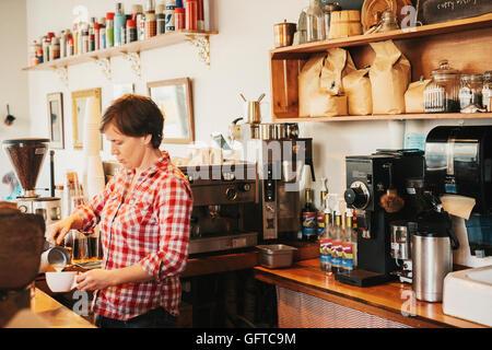 Une femme dans une chemise à carreaux travaillant derrière le comptoir dans un café Banque D'Images