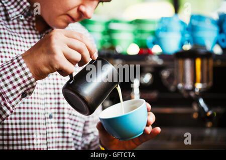 Un homme verser du lait chaud dans une tasse de café pour faire un motif sur le dessus Banque D'Images
