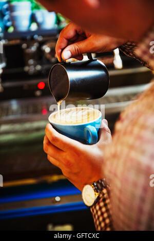 Un barista pouring dans du lait chaud pour la mousse sur une tasse de café pour faire un motif Banque D'Images