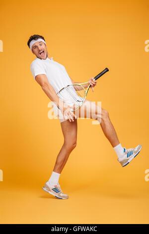Toute la longueur du jeune homme espiègle Funny tennis player s'amusant à l'aide de racket sur fond jaune Banque D'Images
