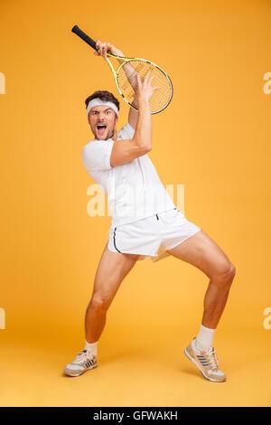 Jeune homme espiègle comique avec joueur de tennis racket en criant et en s'amusant sur fond jaune Banque D'Images