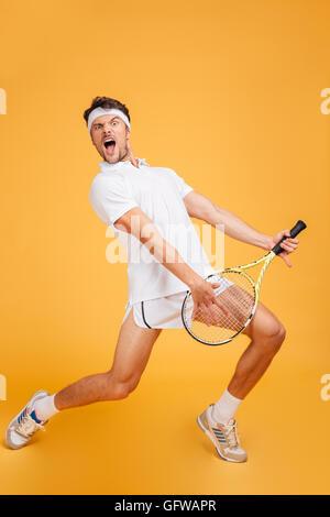 Jeune homme mignon drôle avec le joueur de tennis racket chantant et jouant de la guitare imitant sur fond jaune Banque D'Images