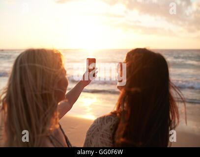 Deux jeunes femmes avec un téléphone mobile pour prendre des photos d'un coucher de soleil au bord de la mer. Les Banque D'Images