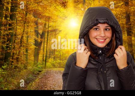 Portrait d'une jeune femme heureuse en randonnée dans une forêt d'automne Banque D'Images