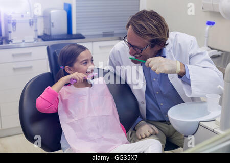 Smiling dentiste et le patient se brosser les dents Banque D'Images