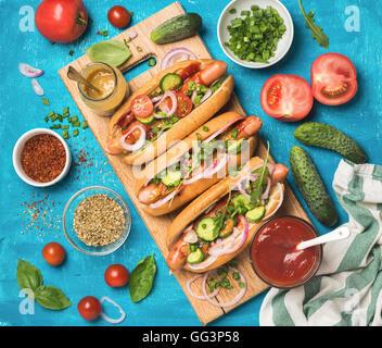 Des hot-dogs avec des légumes frais, épices, le ketchup et la moutarde Banque D'Images