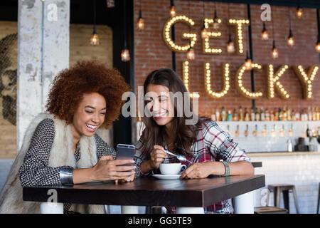 À l'aide d'amis de sexe féminin d'un téléphone intelligent avec café au café Banque D'Images