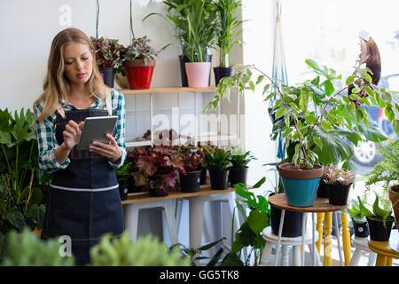 Femme à l'aide d'une tablette numérique à son magasin de fleur Banque D'Images
