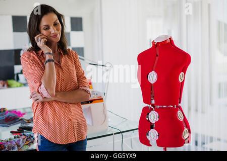 Robe femme designer de parler sur un téléphone mobile dans son bureau Banque D'Images