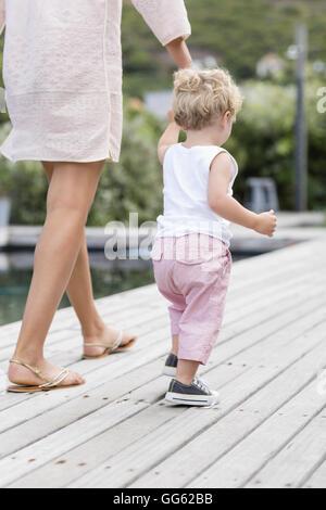 Vue arrière du pied mère avec fils at poolside Banque D'Images