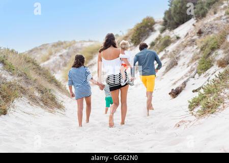 Vue arrière d'une famille marche sur la plage Banque D'Images