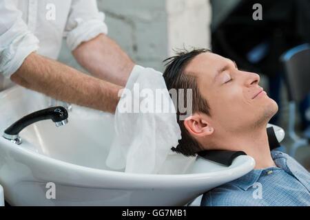 Hairstylist lave-cheveux du client dans la région de barber shop