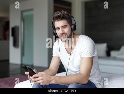 Bel homme à l'écoute de la musique sur tablet par earphones dans appartement de luxe Banque D'Images