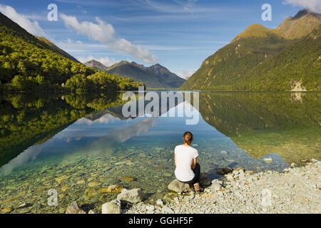 Reflet de la montagne dans le lac Gunn, jeune femme assise au bord du lac, Southland, île du Sud, Nouvelle-Zélande Banque D'Images