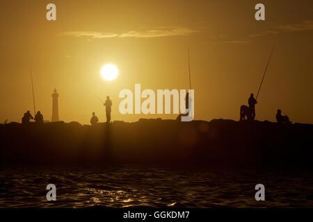 Pêcheurs sur une jetée à Rabat au coucher du soleil, le Maroc Banque D'Images
