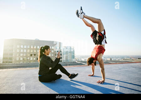 Woman photographing man doing handstand on urban rooftop Banque D'Images