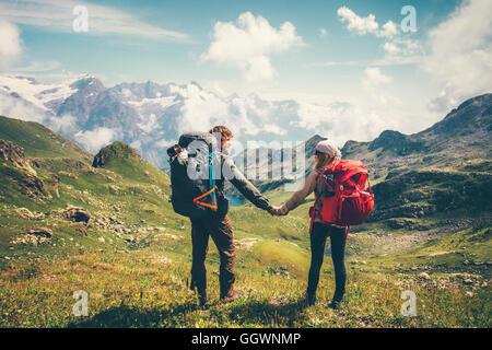 Couple Homme et Femme avec sac à dos alpinisme tenant la main de vie voyage vacances concept montagnes et nuages l Banque D'Images