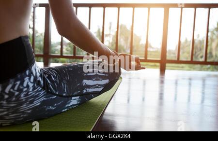 Close up of woman sitting on exercise mat avec les jambes croisées et les mains sur les genoux. Femme méditant dans Banque D'Images