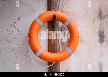 Un gilet de sauvetage orange accrochée à un poste en bois contre un mur de pierre. Banque D'Images