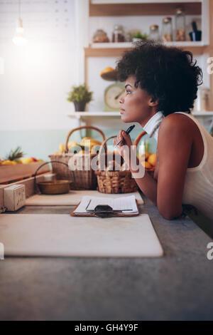 Side portrait of young woman standing au comptoir de bar de jus à l'écart et la pensée. Femme africaine sérieuse bar à jus propriétaire.