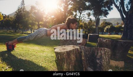Tough young woman doing pushups sur un journal à parc. D'un coup horizontal monter jeunes femmes athlètes exerçant Banque D'Images