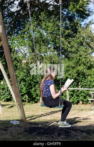 Girl reading in village park, enfant, parc, noir, prairie, arbres, amis, relation, garçon, fille, avant, relaxation, Banque D'Images