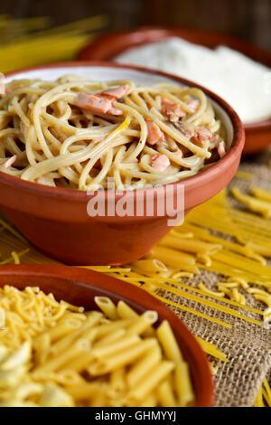 Libre d'une plaque en terre cuite avec quelques pâtes alimentaires non cuites, un bol en terre cuite avec spaghetti Banque D'Images