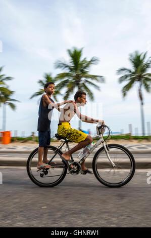 RIO DE JANEIRO - le 6 mars 2016: Paire de jeunes Brésiliens et faire de la bicyclette sur le bord de la plage d'Ipanema Banque D'Images