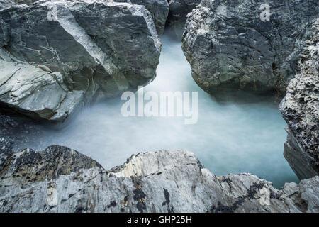 Une longue exposition de la marée sur les rochers au Godrevy en Cornouailles du Nord, Angleterre, RU Banque D'Images