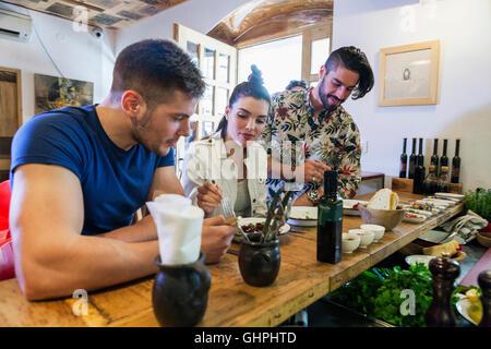 Les jeunes à manger au restaurant counter Banque D'Images