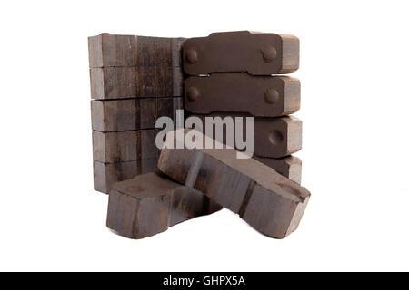 Briquettes de lignite de tour avec deux briques à l'avant, fond blanc, isolé, copiez l'espace, Banque D'Images