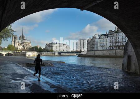 Jogger tournant sous le pont de la Tournelle sur la rive gauche de la Seine, Paris, France Banque D'Images