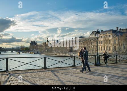 Un couple s'embrasser sur le Pont des Arts sur la Seine avec le Palais du Louvre, Paris, France Banque D'Images