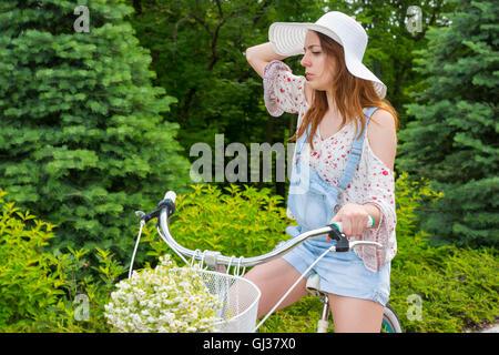 Jeune fille portant un chapeau blanc assis sur son vélo avec un bouquet de fleurs blanches peu dans un panier dans Banque D'Images