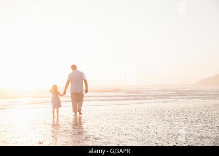 Père et fille se tenant la main en pagayant ocean Banque D'Images