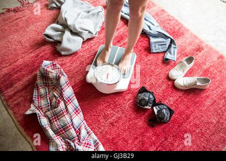 Les jambes de déshabillé Jeune femme debout sur une balance Banque D'Images