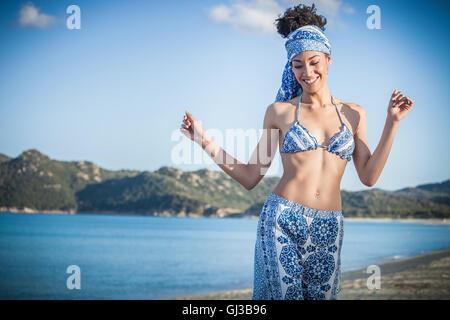 Belle jeune femme wearing bikini top et jupe dancing on beach, Costa Rei, Sardaigne, Italie Banque D'Images