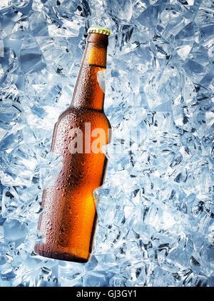 Bouteille de bière brune avec des gouttes sur des cubes de glace Banque D'Images
