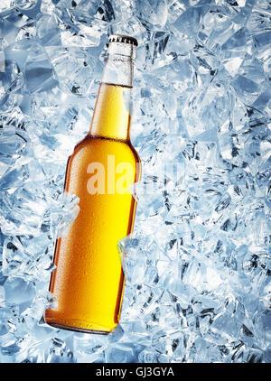 Bouteille de bière de couleur jaune avec des gouttes sur des cubes de glace Banque D'Images