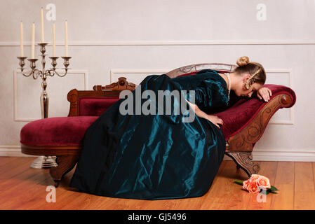 Victorian woman crying on couch Banque D'Images