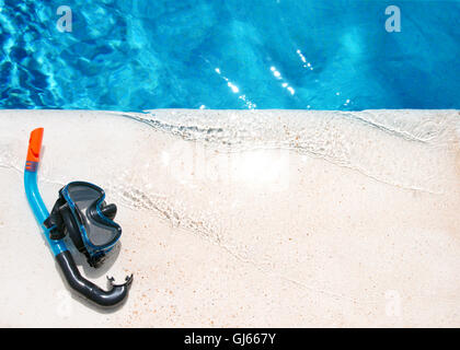 Une paire de lunettes de natation et de la plongée sur une pierre en bord d'une eau cristalline de l'extérieure Banque D'Images