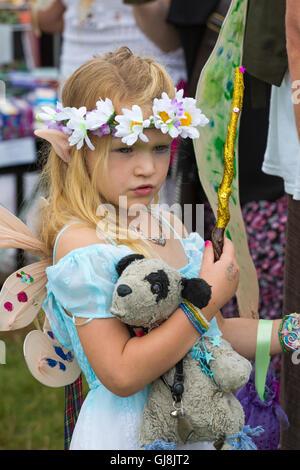 Burley, Hampshire, Royaume-Uni. 13e Août 2016. Jeune fille Fée comme holding toy dog à la nouvelle forêt conte Festival, Banque D'Images