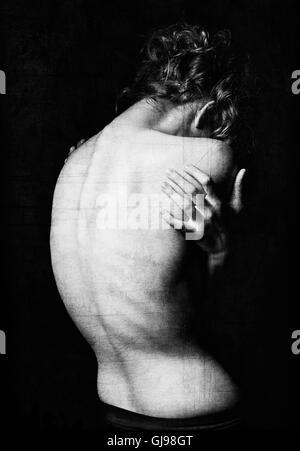 Spooky portrait d'une jeune femme parmi l'obscurité. Effet texture grunge. Noir et blanc, vue arrière Banque D'Images