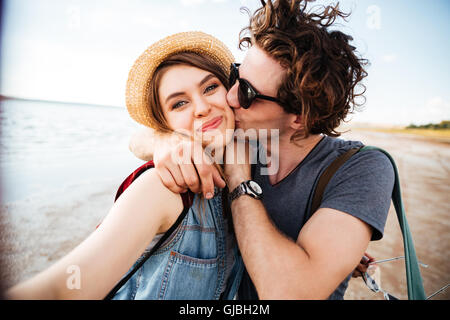 Heureux couple et en tenant l'extérieur selfies Banque D'Images