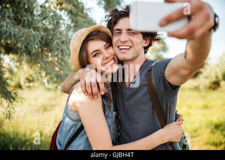 Young smiling couple heureux avec sacs à dos randonnée dans la forêt et faire selfies Banque D'Images